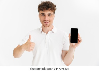 Photo closeup of handsome man in casual t-shirt showing thumb up and holding smartphone screen at camera isolated over white background