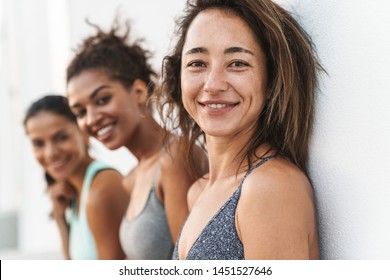 Photo closeup of healthy multiethnic sportswomen in tracksuits smiling at camera and standing over white wall outdoors