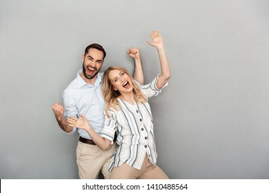 Photo closeup of nice couple in casual clothing smiling and celebrating success isolated over gray wall