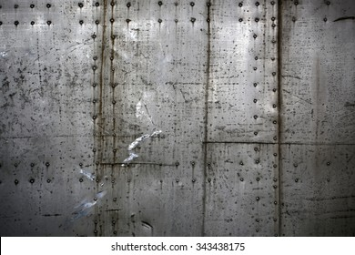 Photo closeup old rusty grunge steel aluminum fragment of protective structure made of metal plates sheets assembled with button head rivets on armor textured background, horizontal picture