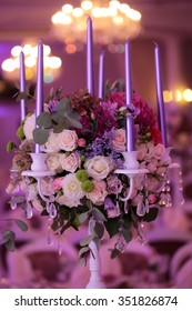 Photo closeup one elegant white candlestick decorated with violet candles crystal strings and fresh colorful flowers green leaves on bokeh background, vertical picture