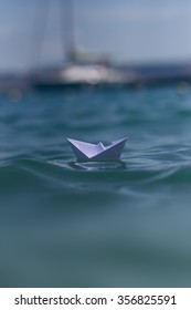 Photo closeup of one little white paper origami boat riding on blue salt sea waves ocean water surface with ripples and yacht on blurred seascape background, horizontal picture