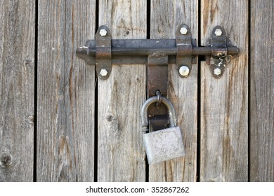 Photo closeup of padlock on old unpainted close boarded gate and fence wooden palisade wood boards with knots on timber background, horizontal picture