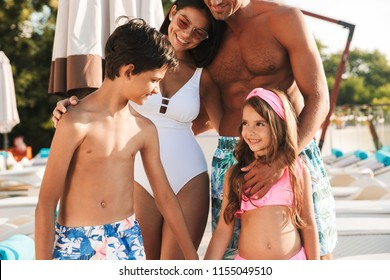 Photo closeup of smiling caucasian family with children resting near luxury swimming pool with white fashion deckchairs and umbrellas during vacation