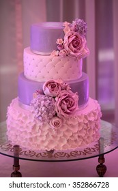Photo closeup of traditional elegant delicious sweet four-layer wedding cake decorated with butter-cream roses on glass stand on blurred violet background, vertical picture