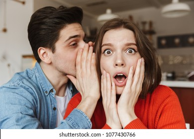 Photo closeup of young woman keeping her hands at face in surprise while man whispering secret in her ear during date in cafe
