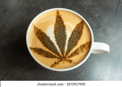Photo of coffee in a mug with cannabis leaf on the top of it.