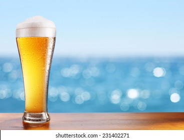 Photo of cold beer glass on the bar table at the open-air cafe.