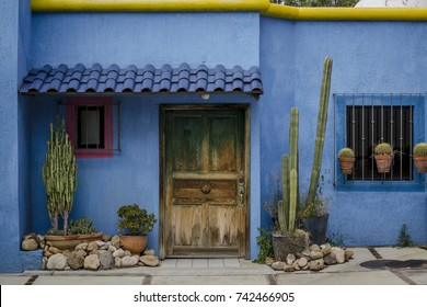 Photo of a colorful happy house, blue walls, yellow roof, red window frame, wooden door and lots of cacti in front. Typical intense colors in the architecture in Guanajuato, Mexico.