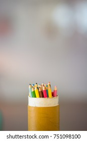 photo of coloured pencils in a can with negative space around and blurred background