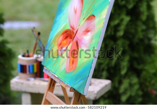 Photo completed and unfinished picture, works of art on which  image multi-colored butterfly on canvas and stands on wooden easel, palette and brush lying near easel, on table stands colorful banks i