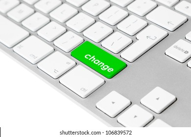 """Photo of a computer keyboard with one green key with the word """"change""""."""