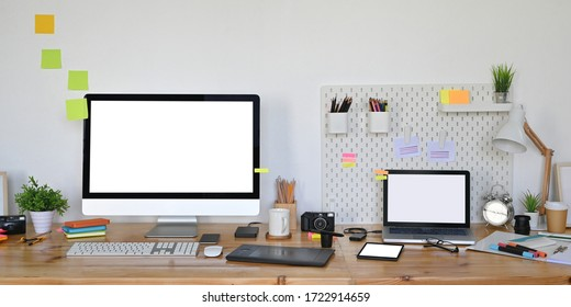 Photo of computer laptop and computer monitor with white blank screen putting on wooden working desk that surrounded by graphic designer equipment over white living room wall as background.