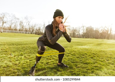Photo of concentrated disabled girl in tracksuit doing sports and squatting with prosthetic leg on grass using resistance band