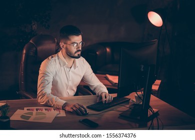 Photo of concentrated focused man pondering over how to outrun his contestants wearing spectacles studying his projects and statistics thoroughly coworking