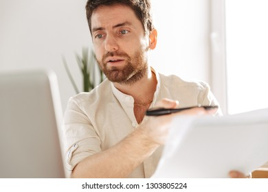 Photo of concentrated office worker 30s wearing white shirt using laptop and paper documents while sitting at table in modern workplace