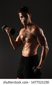 Photo of a concentrated serious handsome young strong sportsman posing isolated over black wall background holding dumbbells make exercises for arms.