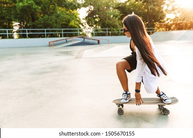 Photo of concentrated young woman in streetwear riding skateboard in concrete park