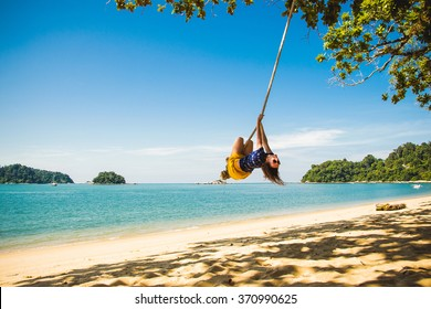Photo of the Concept: enjoyment, happiness and freedom. Freedom woman. Travel concept. Girl having fun swinging on a rope at tropical island beach