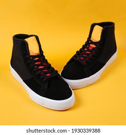 Photo concept of sneakers. Flat style sneakers isolated on yellow background. Fashion sneakers. The classic sneaker. Retro black shoes. Unisex footwear, the sneaker is isolated on the background