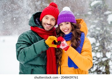 Photo of confident charming marriage couple wear windbreakers embracing walking snowy weather smiling outside park