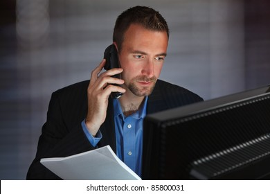 Photo of a confident young businessman working at his computer while talking on the phone and holding paperwork