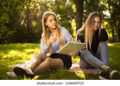Photo of confused displeased young beautiful ladies students sitting in the park outdoors on grass holding copybook doing homework.