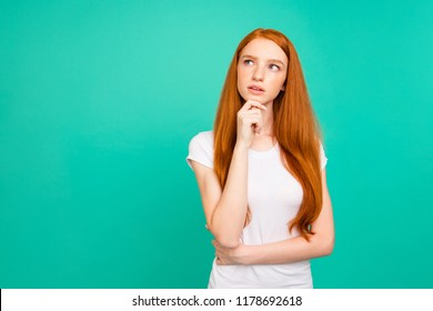 Photo of confused person with long hair, stand in white t-shirt and look aside touch chin by hand isolated on vivid teal background with copy space for text