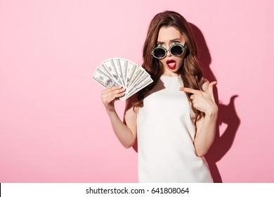 Photo of a confused young brunette woman in white summer dress holding money pointing and looking at camera over pink background.
