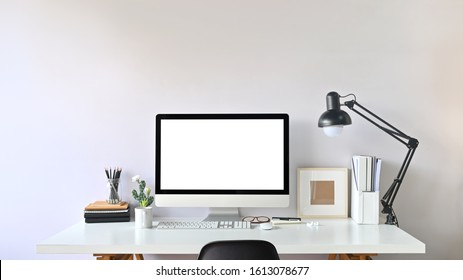 Photo of Contemporary Workspace. White blank screen monitor on modern working desk. Equipment on table. Modern office concept.
