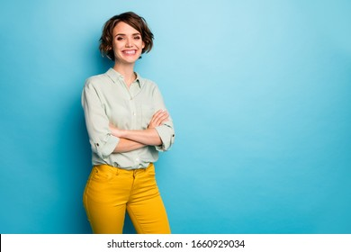 Photo of cool attractive business lady short hairstyle friendly beaming smiling arms crossed good mood wear casual green shirt yellow pants isolated blue color background