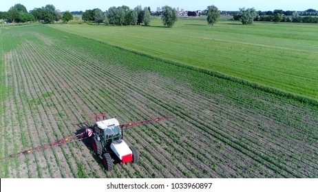 Photo corn field tractor spraying agrochemical or agrichemical over young maize field in most cases agrichemical refers to pesticides like insecticides herbicides fungicides and nematicides