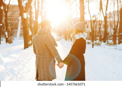 Photo of a couple walking, and holding hands, on a sun lights background