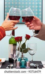 Photo of a couples hands toasting their glasses of red wine over the table in a restaurant