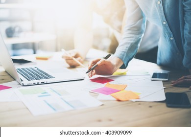 Photo coworking team meeting. Young business crew working with new startup project in studio. Modern notebook on wood table. Using marketing plans,sales reports. Horizontal, film  effect - Shutterstock ID 403909099