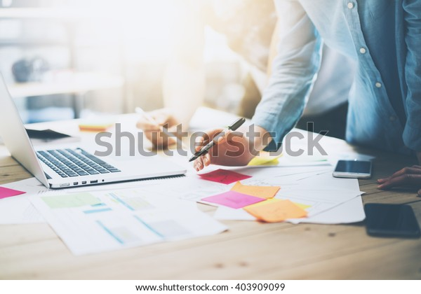 Photo coworking team meeting. Young business crew working with new startup project in studio. Modern notebook on wood table. Using marketing plans,sales reports. Horizontal, film  effect