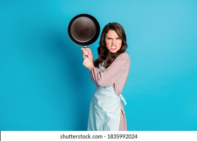 Photo of crazy angry mad outraged lady hold hands kitchen utensil frying, pan cooking dinner fight boyfriend beating him wear apron dotted dress isolated blue color background