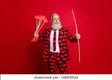 Photo of crazy cupid mature handsome guy valentine day hold bow arrow ready to shoot loving couple wear hearts pattern stylish suit tie trousers blazer isolated red color background