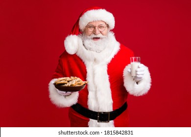 Photo of crazy funky santa claus hold x-mas tradition ginger bread cookies plate milk glass wear red costume headwear isolated over bright shine color background
