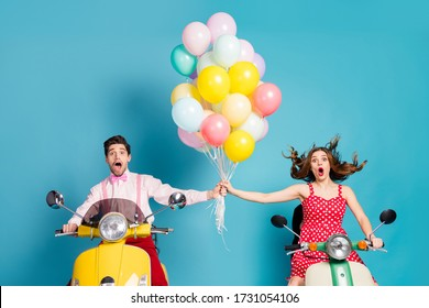 Photo of crazy shocked two people lady guy drive retro moped travelers hold raise hands many air balloons birthday guests fly up wind vintage clothes isolated blue color background
