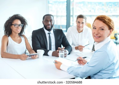 Photo of creative multi ethnic business group. Mixed race business team using electronic devices and discussing project. Accent on leader of group. White modern office interior with big window