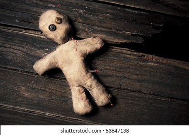 photo of creepy voodoo doll on wooden floor