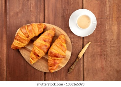 A photo of croissants with coffee and a vintage knife, shot from above on a dark rustic wooden background with a place for text