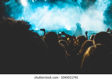A photo of a crowd during a indie rock concert at a summer festival. The smoke illuminated blue. You can see people recording the performance with their smart phones.