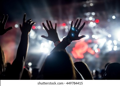 Photo of a crowd, people enjoying rock concert, raised up hands and clapping of pleasure, active night life concept.