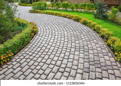 Photo of a curved alley of stone bricks in a city park among green spaces