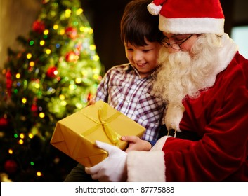 Photo of cute boy and Santa Claus holding giftbox and looking at it