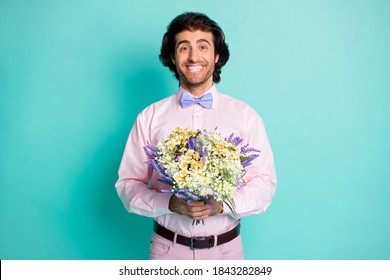 Photo of cute cheerful wavy hair man dressed pink outfit presenting you bunch fresh flowers romantic date isolated teal color background