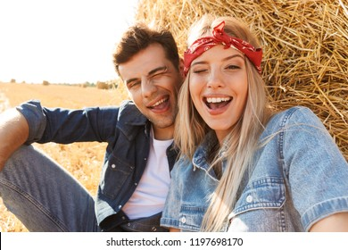 Photo of cute couple man and woman smiling while sitting under big haystack in golden field during sunny day
