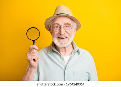 Photo of cute funny mature man dressed green shirt cap glasses smiling holding loupe isolated yellow color background